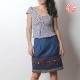 Short supple blue denim skirt with various trims and fringes