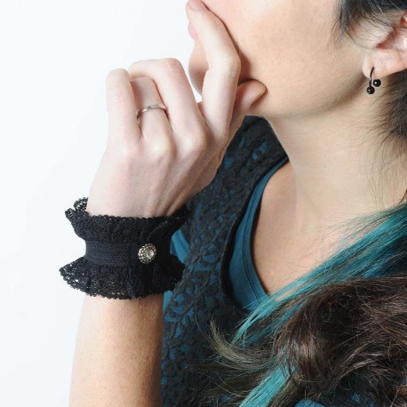 Short black bracelet cuffs, lace ruffles and rhinestone
